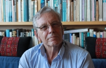 """Amos Oz in his Tel Aviv apartment. His bestselling memoir, """"A Tale of Love and Darkness,"""" is on the bookshelf behind him, translated into more than two dozen languages."""