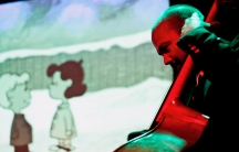 """""""A Charlie Brown Christmas"""" plays on screen behind a live band."""