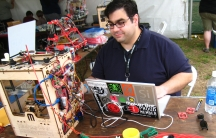 A man operates a 3D printer at a 2010 Maker Faire, a gathering for maker movement enthusiasts, in New York City.
