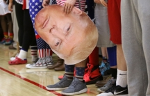 Fans legs, one holding a large poster of Trump's face