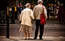 An elderly couple holds hands while waiting to cross a London street.