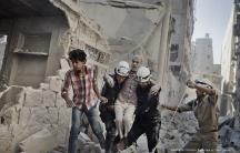Members of the Hanano team rescue a man who had been trapped inside his home after a bomb hit it in Aleppo, Syria.