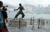 Filmmaker Mark Cousins during this six-year filming of The Story of Film, shooting the skyline of Hong Kong with a statue of hometown hero and martial artist Bruce Lee in the foreground.