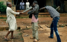 Muslim men organized in militias with machetes rough up a Christian man while checking him for weapons in the Miskine neighborhood of Bangui, Central African Republic.