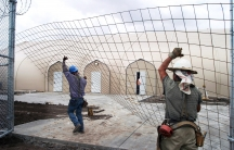 Workers raise a fence in front of white kevlar tents