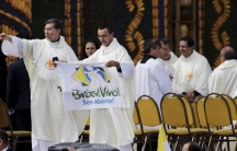 "A priest holds up a banner reading ""Brazil alive! Without abortion"" while standing near an altar where Pope Francis later celebrated mass."