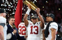 A man in a football jersey holds a trophy over his head as confetti rains down behind him.