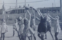 A group of children jump and reach for a ball on a volleyball court at a refugee camp in Germany after World War II