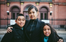Angela Navarro and her two children stand outside the church where they've been living since mid-November.