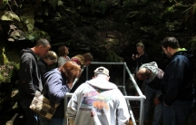 Tourists crowd around the pit in the Coudersport Ice Mine, a Pennsylvania tourist attraction where ice only forms during the summer.