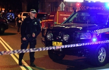 Police man stands at a check point next to a police car in the Sydney inner suburb of Surry Hills