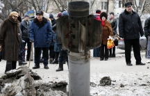 People look at the remains of a rocket shell on a street in the town of Kramatorsk, eastern Ukraine February 10, 2015.