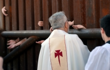 People on the Mexican side of the border reach through fence in Nogales, Arizona, to receive Holy Communion from the Bishop of Tucson, Gerald Kicanas.