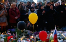 People gather at the Place de la Bourse to pay tribute to the victims of bomb attacks in Brussels.