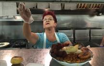 The owner of El Peñol restaurant in East Boston with a bandeja paisa.
