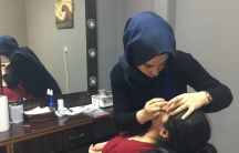 Elif Koc, 18, shapes a customer's eyebrows at the Twins salon in Istanbul. Kroc is voting yes on Sunday's referendum. But she says the issue is dividing her family.