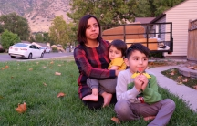 Woman sitting on grass in front of building with two young children in front of her