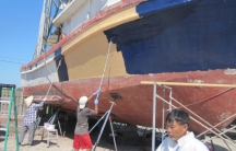 Sang Ho and crew paint his shrimping boat for shrimping season. He now also farms in addition to shrimp fishing.