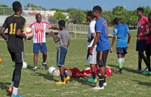 Ernst Baptiste, coach of the Little Haiti Football Club boys team, directs his players onto the field to start drills.
