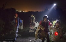 Thousands of migrants and refugees arrive daily by train into Tabonovzce, Macedonia, on their way north. Volunteers with flashlights illuminate their path as they walk to an informal crossing point into Serbia.