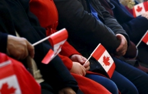 Syrian refugees hold Canadian flags