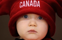 Sixteen-month-old Canada fan Rogan Clark watches team Canada and team Switzerland warm up before their exhibition hockey game in Red Deer, Alberta.