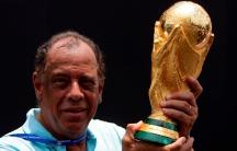Former Brazilian soccer captain Carlos Alberto Torres holds the FIFA World Cup trophy in Rio de Janeiro on Nov. 21, 2010.