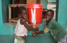 Children in Lower Johnsonville, Liberia, wash their hands