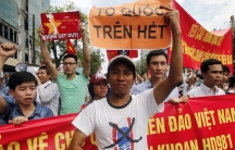 """A protester holds a placard reading """"nation first"""" during an anti-China protest in Hanoi to denounce China's setting up of a giant oil rig in the South China Sea."""