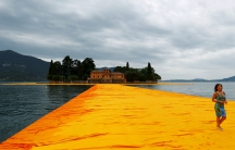 "A woman walks on the installation ""The Floating Piers"" by Bulgarian-born artist Christo Vladimirov Yavachev known as Christo, on Lake Iseo, northern Italy."
