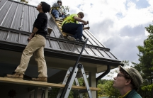 Solar Holler founder Dan Conant, foreground, looks on at the beginning of a solar roof installation in Lewisburg, West Virginia.