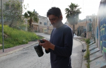 Emad Abu Shamsiyeh who filmed the shooting, standing with his camera at the site in Hebron where it happened. Since his video was posted online, he's been threatened and attacked.