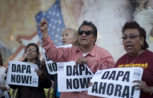 "One man and three women hold signs that say ""DAPA now!"" and ""DAPA Ahora!"" before a wall covered with a mural, barely visible."