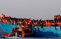 A rescue boat of the Spanish NGO Proactiva approaches an overcrowded wooden vessel with migrants off the Libyan coast in Mediterranean Sea.