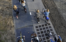 Cyclists ride over a 230 feet stretch of a new bike made entirely of solar panels in The Netherlands.