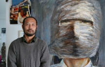 Hu Jie is also a painter, standing here in his Nanjing apartment next to a portrait of one of the subjects of his films, Lin Zhao, a political prisoner who was executed in the late 1960s.