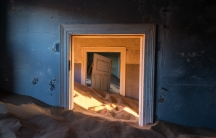 A doorway half-buried by sand in Kolmanskop, Namibia