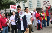 Daniel Meza holds a bullhorn as Mario Sidonio, to his right, waits his turn to speak at a rally in front of Houston's City Hall.