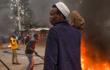 A man holds a large stone during a protest in Nairobi, Kenya.