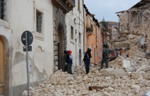 Emergency workers inspect the earthquake damaged buildings in L'Aquila Italy in April, 2009.