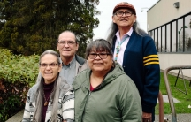 Two men and two women stand together next to a court house.