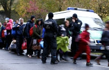 Newly arrived migrants are cleared by German police officers after crossing the Austrian-German border from Achleiten, Austria, into the city of Passau, Germany on October 29, 2015.