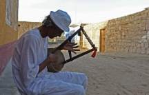 A man plays music on a traditional musical instrument in the Nubian village of Adindan