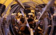 Policemen and soccer fans are seen through barbed wire as fans attempt to enter a stadium to watch a match, on the outskirts of Cairo February 8, 2015.