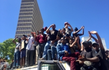 Protesters atop a police van in Cape Town last month