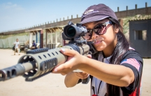 Claudia Vidanes aims a Phatom Strike AR-15, a custom gun designed by her father, Jojo Vidanes, who is the president of the Norco Running Gun Club in California.