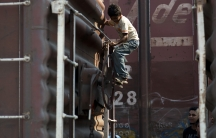 A child boards a freight train near Arriaga, Chiapas, in southern Mexico. Arriaga is the first stop for many Central American migrants making their way to the US.