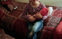 Five-year-old Leen, a Syrian refugee, poses for a portrait with her doll in her Sacramento, California bedroom on November 16, 2015. Her face is not being shown for security reasons.