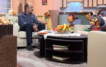 Mr. Host reading a book with the puppets of Kolah Germezi, including the sheep Babayi.
