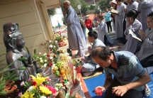 Vietnamese immigrants pray to a small shrine erected five years ago. The area was once littered, covered in graffiti, and a frequent stop for the city's public works department. But after one neighborhood resident placed the statue on the corner, local Vi